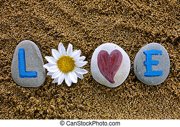 Love spell out from stones with letters, heart and flower - ...