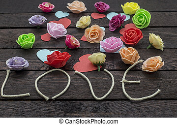 Word love with beautiful flowers on the brown background