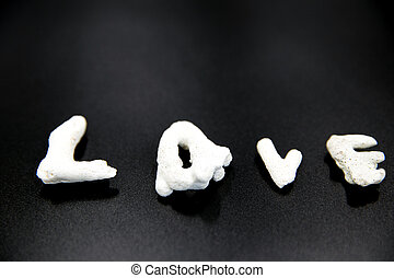 Word Love with coral stone on black background.