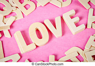 Word LOVE wooden on pink background.