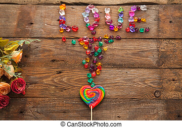 "Word ""love"" written with colorful stones and lollipop in the shape of a heart"
