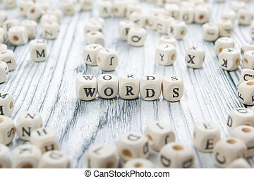 Word made with block wood letter next to a pile of other letters over the wooden board surface composition. Block ABC