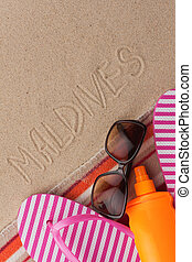 Word MALDIVES written in sand with beach accessories.