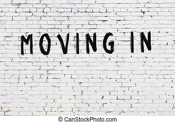 Word moving in painted on white brick wall