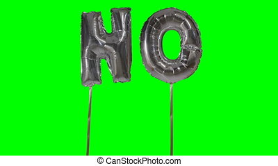 Word no from helium silver balloon letters floating on green...