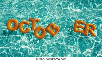 "word ""OCTOBER"" shaped inflatable swim ring floating in a..."