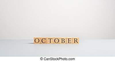 Word October spelled on wooden cubes