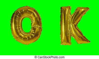 Word ok from helium gold balloon letters floating on green...