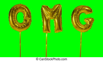 Word OMG from helium golden balloon letters floating on...