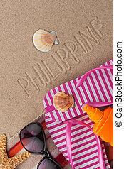 Word PHILIPPINE written in sand with beach accessories.