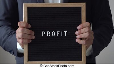 Word Profit from Letters on Text Board in Anonymous Businessman Hands