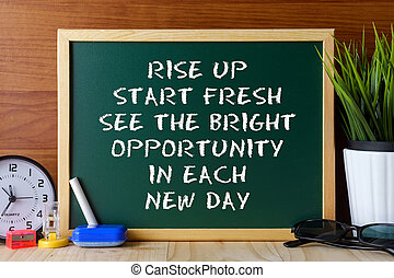 Word quote RISE UP START FRESH SEE THE BRIGHT OPPORTUNITY IN EACH NEW DAY written on green chalk board on wooden table.