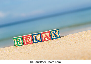 word RELAX in colorful alphabet blocks on tropical beach