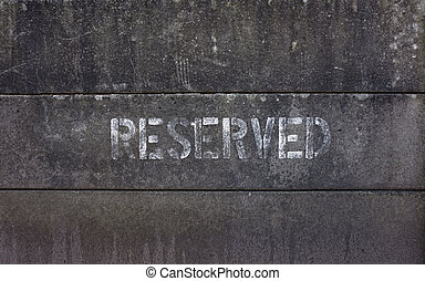 Word reserved spray painted on concrete blocks fence