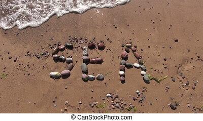 word sea written on beach sand