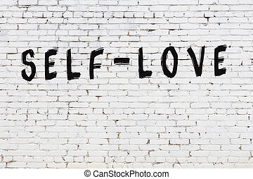 Word self-love painted on white brick wall
