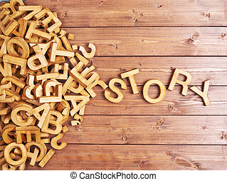 Word story made with block wooden letters next to a pile of other letters over the wooden board surface composition