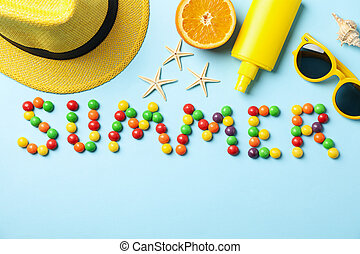 Word Summer and vacation accessories on blue background, top view
