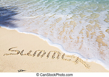 Word SUMMER on sandy beach - vacation concept background