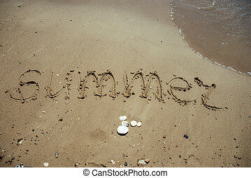 Word Summer written on sandy beach.