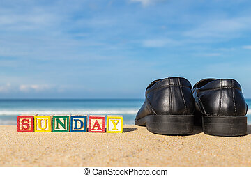 word SUNDAY in colorful alphabet blocks and black shoe on tropical beach