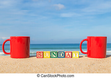 word SUNDAY in colorful alphabet blocks and coffee cup on tropical beach