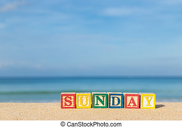 word SUNDAY in colorful alphabet blocks on tropical beach