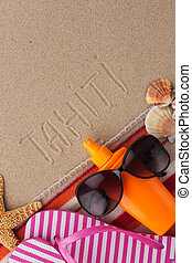 Word TAHITI written in sand with beach accessories.