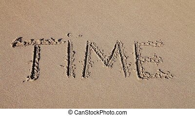 "Word ""Time"" drawn in the sand"