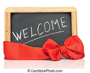"""word """"welcome"""" - white chalk handwriting on small school wooden blackboard with red bow"""