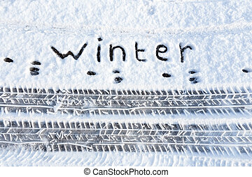 Word winter and tire tracks in snow