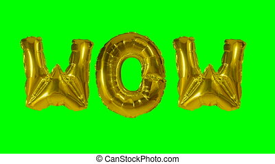 Word wow from helium gold balloon letters floating on green...