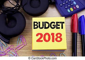 Word, writing Budget 2018. Business concept for Household budgeting accounting planning written on sticky note paper on the wooden background. With calculator and pen marker and headphones