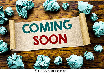 Word, writing Coming Soon. Business concept for Message Future Written on sticky note paper, wooden background with folded yellow paper meaning thinking