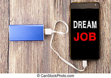 Word, writing Dream Job. Business concept for Dreaming about Employment Job Position written on mobile cell phone mobile and power-bank charger on old wood wooden background