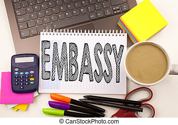 Word writing Embassy in the office with laptop, marker, pen, stationery, coffee. Business concept for Tourist Visa Application Workshop white background with copy space