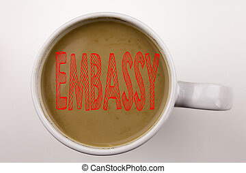 Word, writing Embassy text in coffee in cup. Business concept for Tourist Visa Application on white background with copy space. Black text with red word.