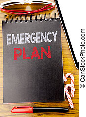 Word, writing Emergency Plan. Business concept for Disaster Protection Written on the notebook book, wooden background with sticky sunglasses and red pen