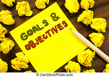 Word, writing Goals Objectives. Business concept for Plan Success Vision Written on sticky note paper, wooden background with folded yellow paper meaning thinking