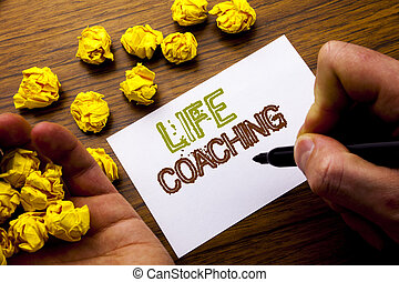 Word, writing Life Coaching. Concept for Personal Coach Help written on notebook note paper on the wooden background with folded paper meaning thinking for idea. Man hand and marker.