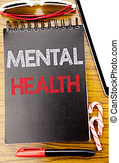 Word, writing Mental Health. Business concept for Anxiety Illness Disorder Written on the notebook book, wooden background with sticky sunglasses and red pen