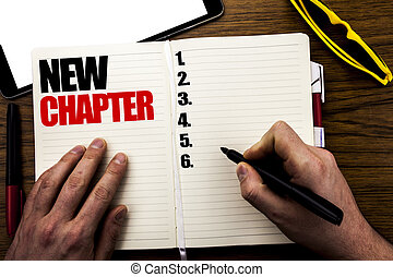 Word, writing New Chapter. Business concept for Starting New Future Life Written on book, wooden background with businessman hand, finger writing on the notebook.