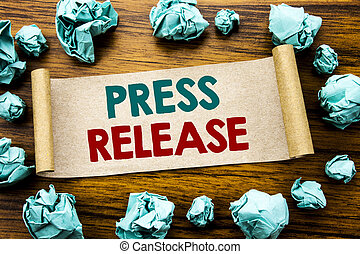 Word, writing Press Release. Business concept for Statement Announcement Message Written on sticky note paper, wooden background with folded yellow paper meaning thinking