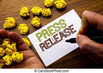 Word, writing Press Release. Concept for Statement Announcement Message written on notebook note paper on the wooden background with folded paper meaning thinking for idea. Man hand and marker.