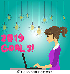 Word writing text 2019 Goals. Business concept for something you hope to achieve or get in near or far future photo of Young Busy Woman Sitting Side View and Working on her Laptop.