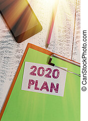 Word writing text 2020 Plan. Business concept for setting up your goals and plans for the current year or in 2020 Clipboard sheet pencil smartphone squared sticky note wooden background.