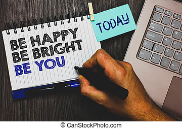 Word writing text Be Happy Be Bright Be You. Business concept for Self-confidence good attitude enjoy cheerful Paperclip grip sticky note with text hand hold pen computer on wooden desk