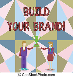 Word writing text Build Your Brand. Business concept for creates or improves customers knowledge and opinions of product Man and Woman in Business Suit Holding Together the Championship Trophy Cup.