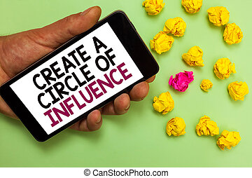 Word writing text Create A Circle Of Influence. Business concept for Be an influencer leader motivate other people Man holding cell phone white screen looking messages crumpled papers.