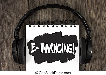 Word writing text E-Invoicing Motivational Call. Business concept for Company encourages use of digital billing written on Notepad on the wooden background Headphone next to it.